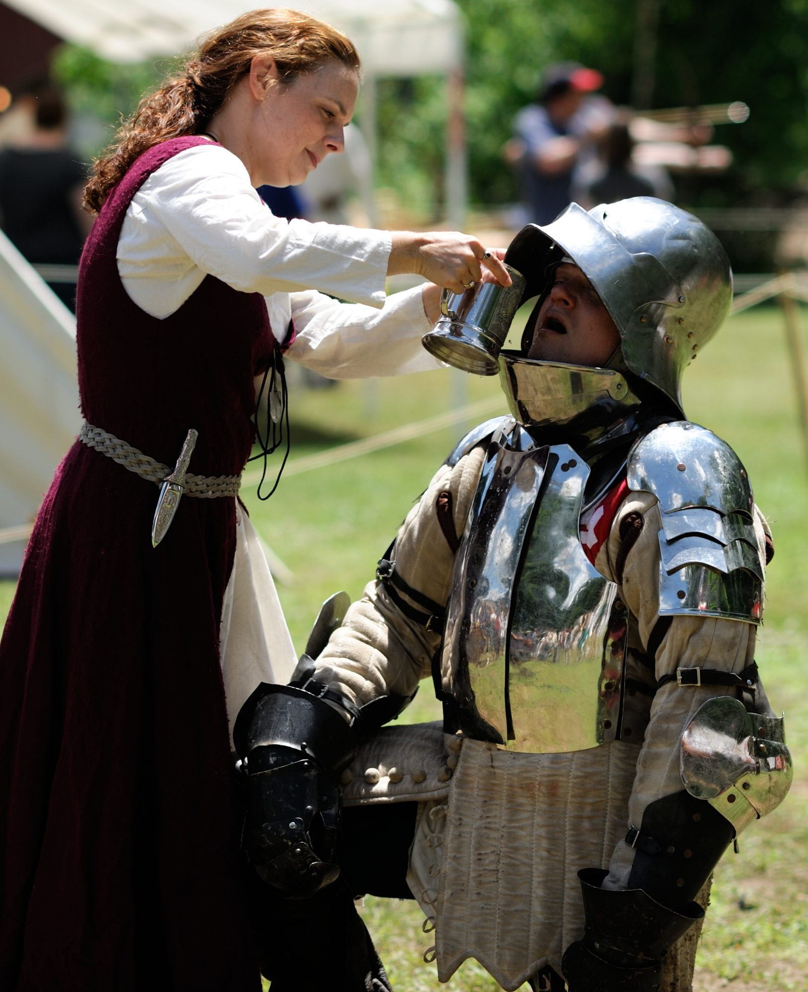 Man in armor gets a drink from a wench