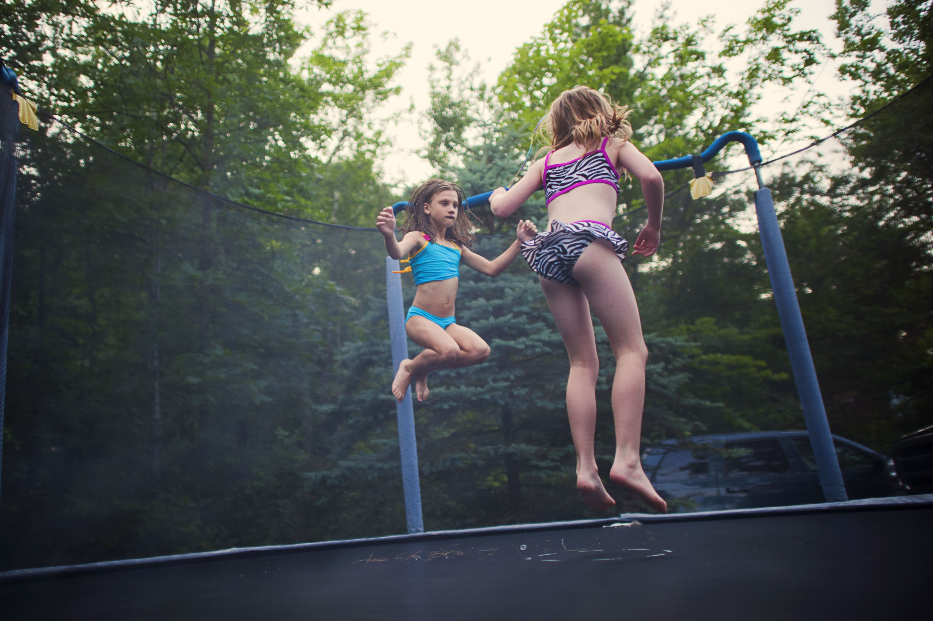 Two girls in swimsuits jumping on a trampoline.