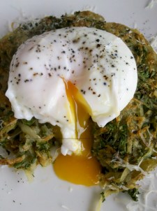 Breaking the egg on a stack of kale and potato hash with parmesan cheese