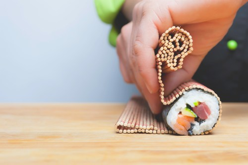 closeup of chef hands rolling up sushi on a bamboo mat