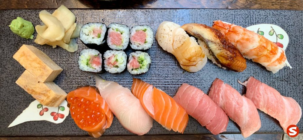 tamago (egg omelet), maguro (tuna back) maki (roll), hotategai (scallop), unagi (freshwater eel), ebi (shrimp) nigiri, sake (salmon) gunkan (battleship sushi) with ikura (salmon roe), hamachi (yellowtail), sake (salmon), otoro (fatty tuna belly), chu-toro (medium fatty tuna belly) nigiri plate