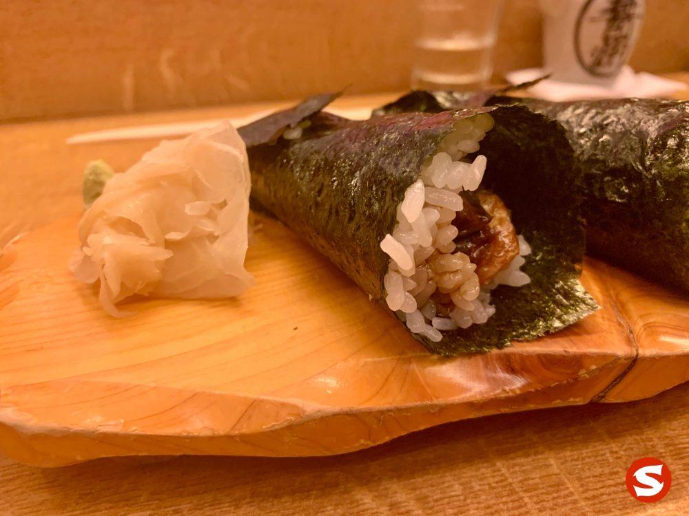 sake cava temaki (handroll with grilled salmon skin) with gari (pickled ginger)