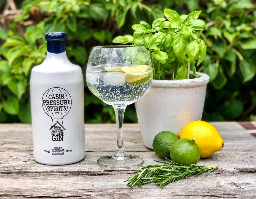 Gin bottle with gin and tonic, lemon and limes