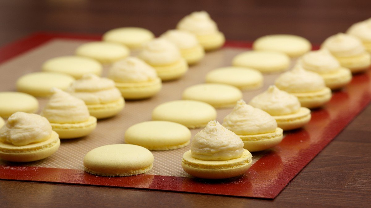 Macaroon halves on a silicone baking mat