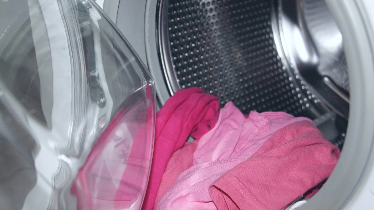 pink clothing in waching machine with the doors open