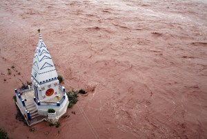 A temple stands amid the waters of the flooded river Tawi after heavy rains in Jammu
