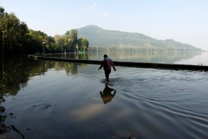 A man wades through a flooded road along the banks of Dal Lake in Srinagar