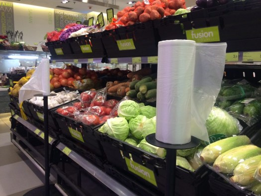 Photo of a typical supermarket scene showing fruit and vegetables and rolls of plastic produce bags.
