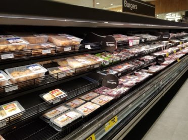 A photo of the meat isle in a supermarket showing the extent of plastic pollution packaging.