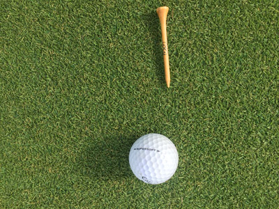 putting green turf with golf ball and golf tee