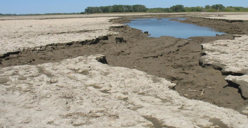 dry soil on left with a standing pool of water and severely eroded land on the right