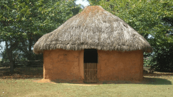 A small structure has a thatched roof and smooth mud walls. An opening faces us with a small wooden gate.
