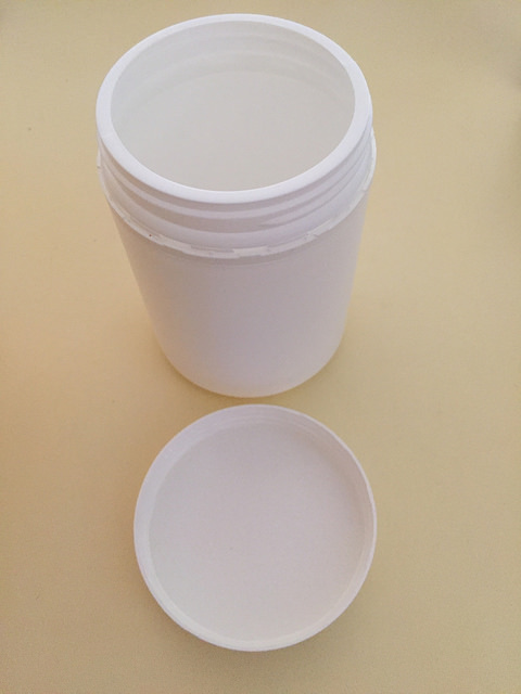 Empty white plastic cylindrical container with screw top lid