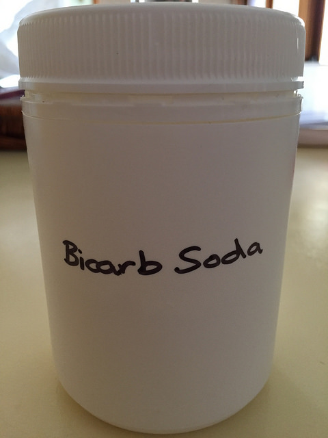 White cylindrical plastic container labelled Bicarb Soda, with lid