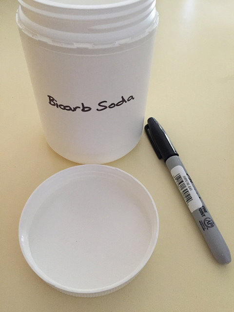 White plastic cylindrical container (labelled), lid & felt-tipped marker pen