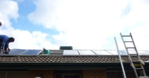 the first row of solar panels being installed on the roof