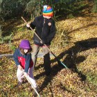Two children wearing beanies and weilding rakes, on a leafy lawn