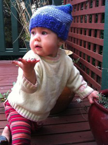 """One year old Eliane modelling her square beany, and holding up for hand as if to say """"what""""?"""
