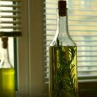 Attractive bottle of olive oil with several sprigs of rosemary inside.