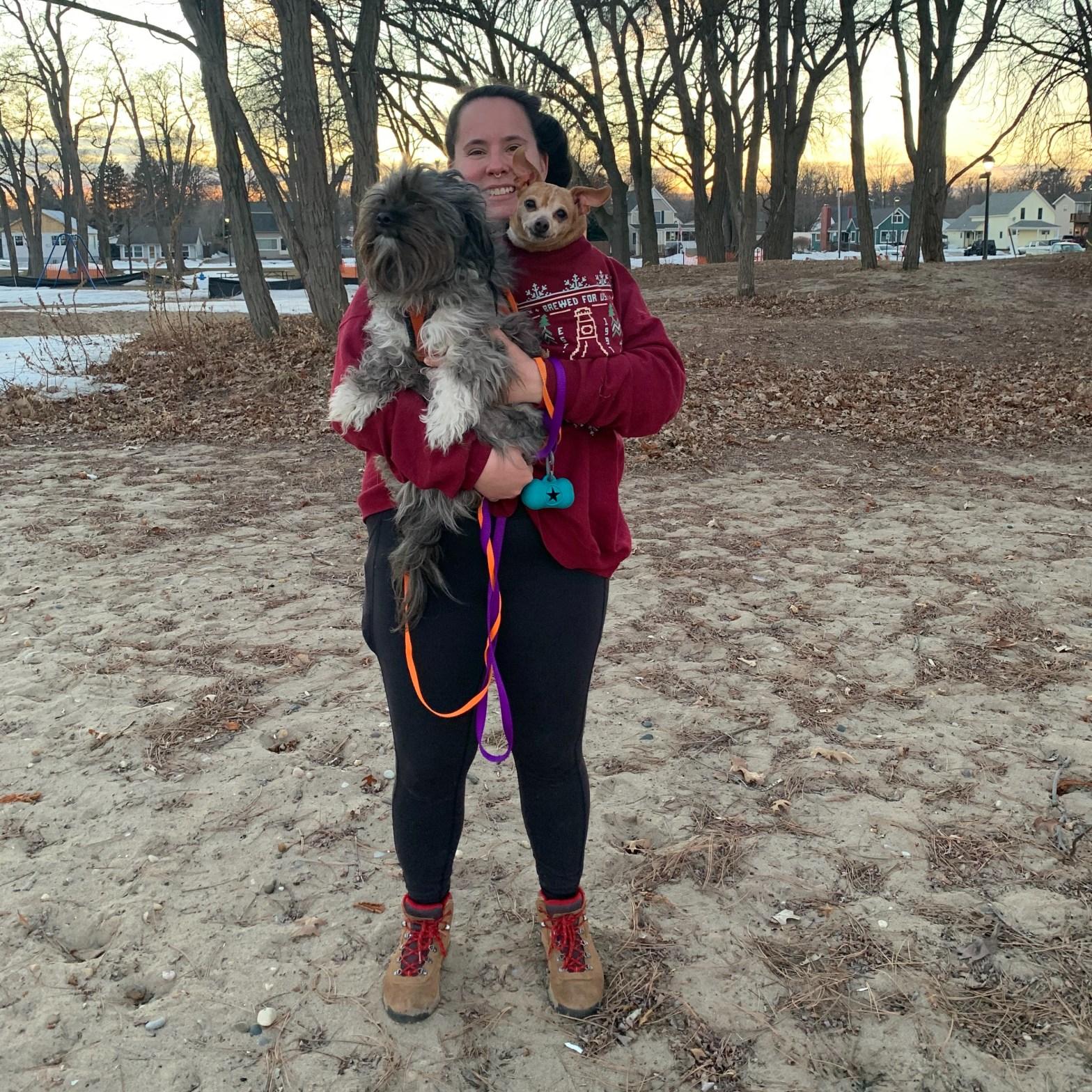 Sara holding the dogs on beach