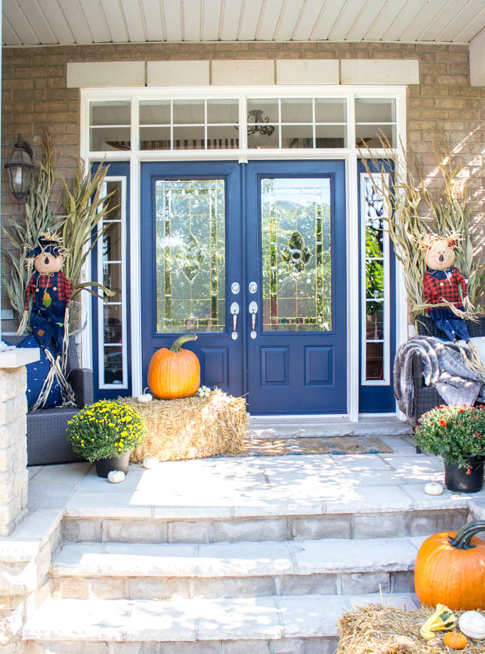 a fall front porch decorated with hay bales orange pumpkins mums cornstalks and