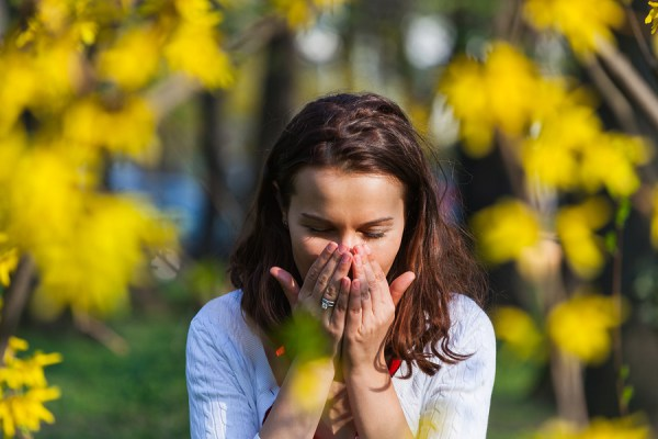 Woman with a flu or an allergy is sneezing while standing outside in a park