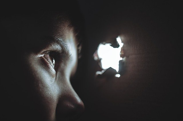 Image of a boy looking out of a bullet hole