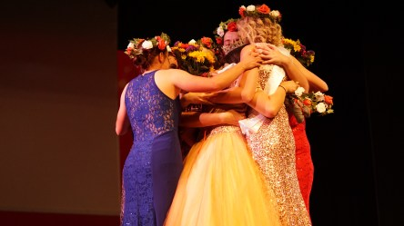 Miss SUU contestants hugging on stage.