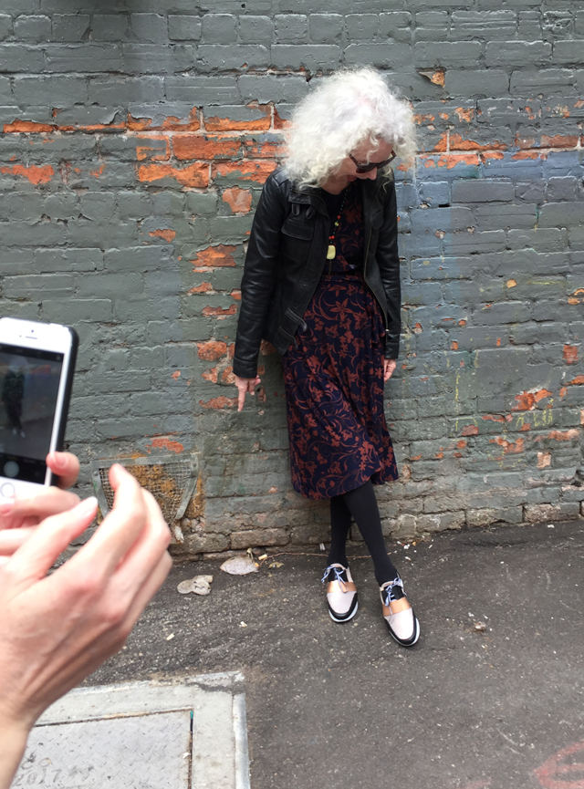 patti not dead yet style taking a photo in an alley