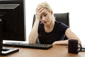 woman sitting at her desk with her head in her hands stressed out