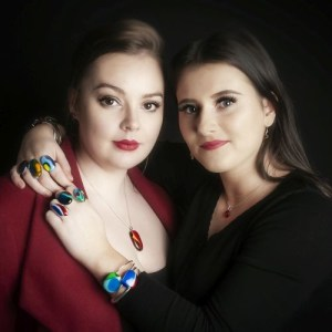 Two models wearing glass jewelry