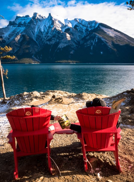 devour-cao-ab-landmark-banff-lake-minnewanka-with-red-chairs-sharing-jerky-3-edited