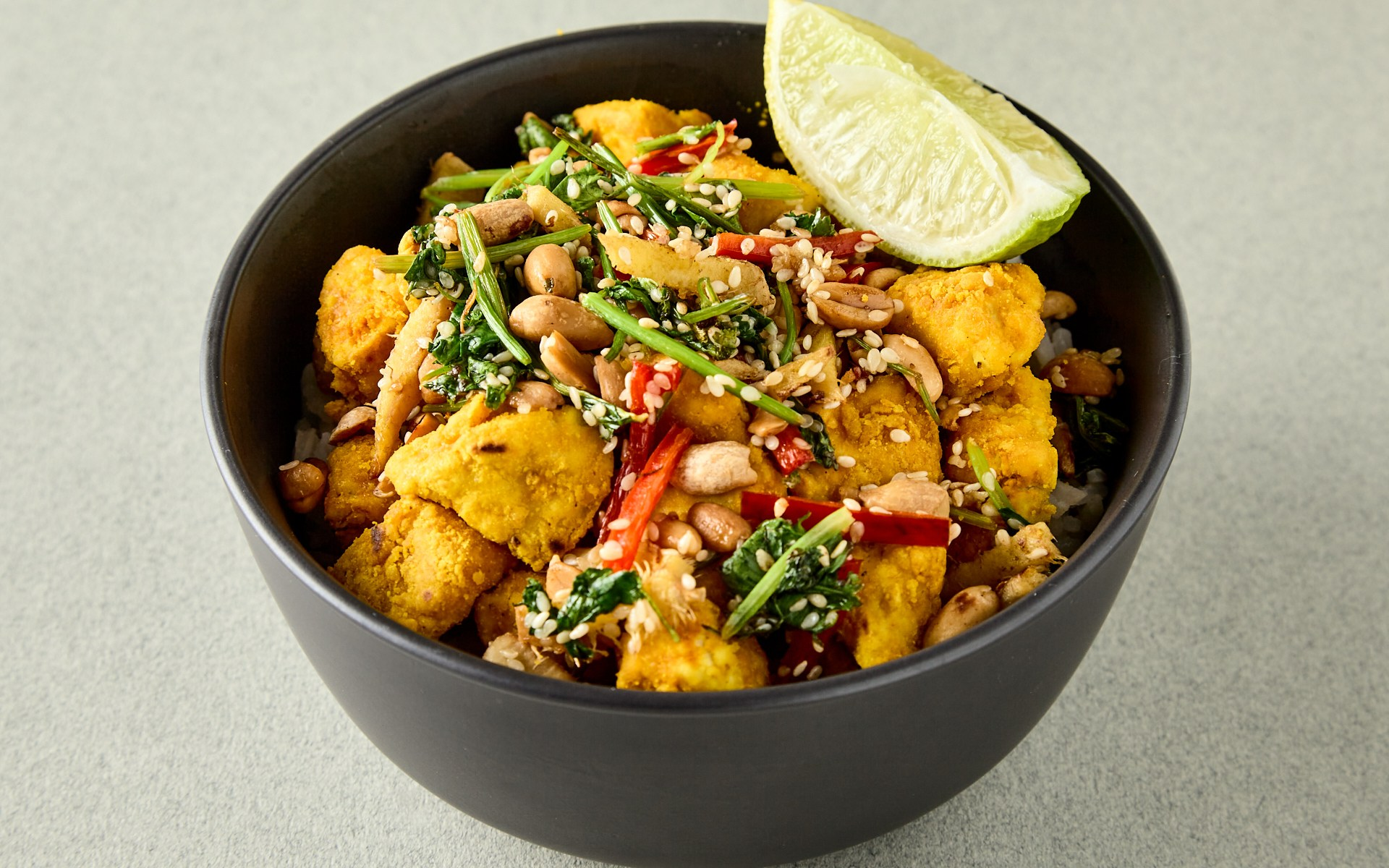 Black bowl containing turmeric tofu, chopped greens and a lime wedge