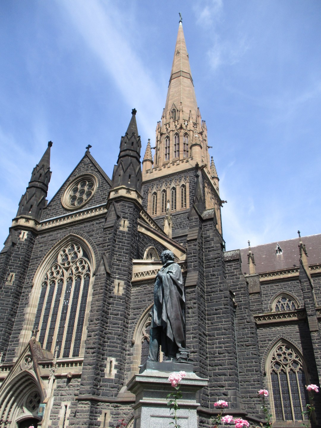 Gothic style St Patrick's cathedral in Melbournewith dark stone brickwork and blue skies behind