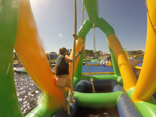 GoPro image of girl taking on inflatable water park challenge in Australia