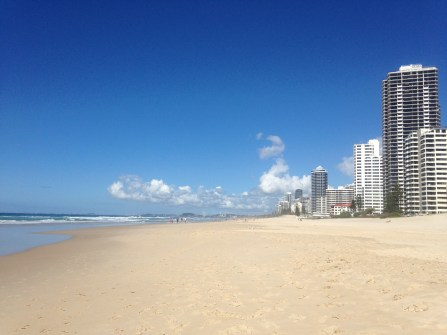 Perfect gold empty beach with blue skies adjacent to skyscraper flats