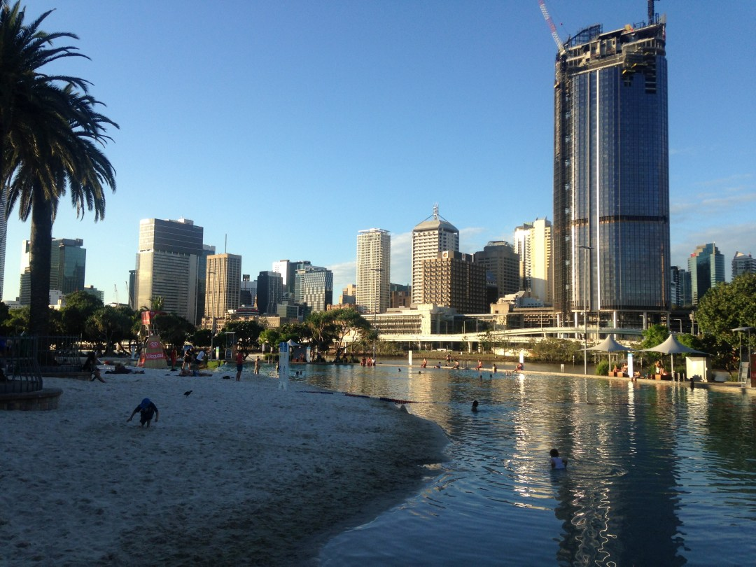 Brisbane Southbank overlooking the beachy area and pool with the sky scrapers in the background during sunset