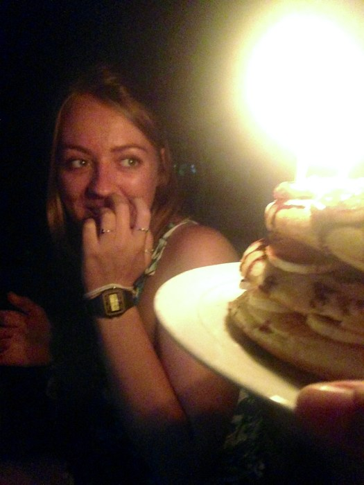 "Girl smiles as she is presented with birthday ""cake"" pancakes"