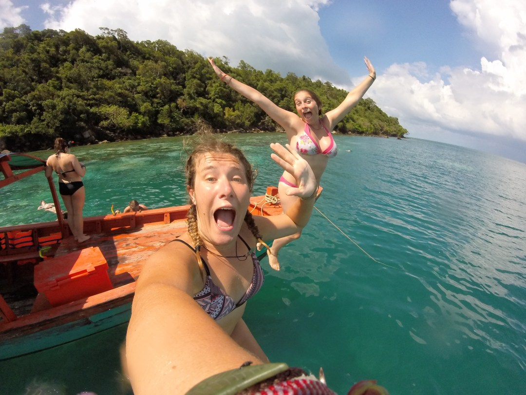 Girls jump off a boat and into blue waters
