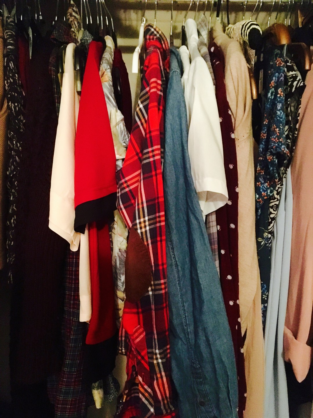 assortment of clothes hanging on rail