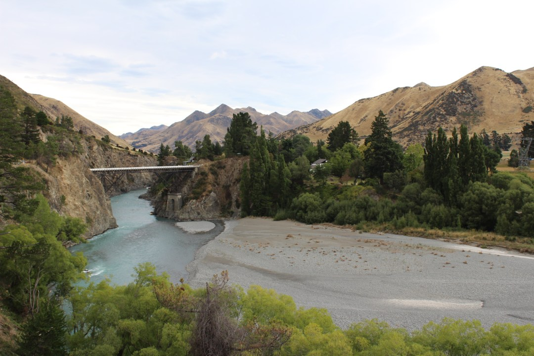 bridge over river with mountains behind