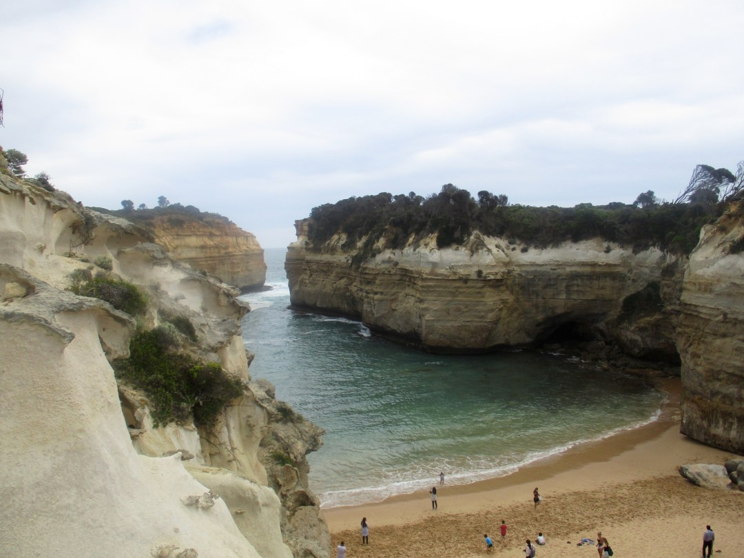 Tall stone walls open a narrow bay to a sandy beach at Loch Ard Gorge