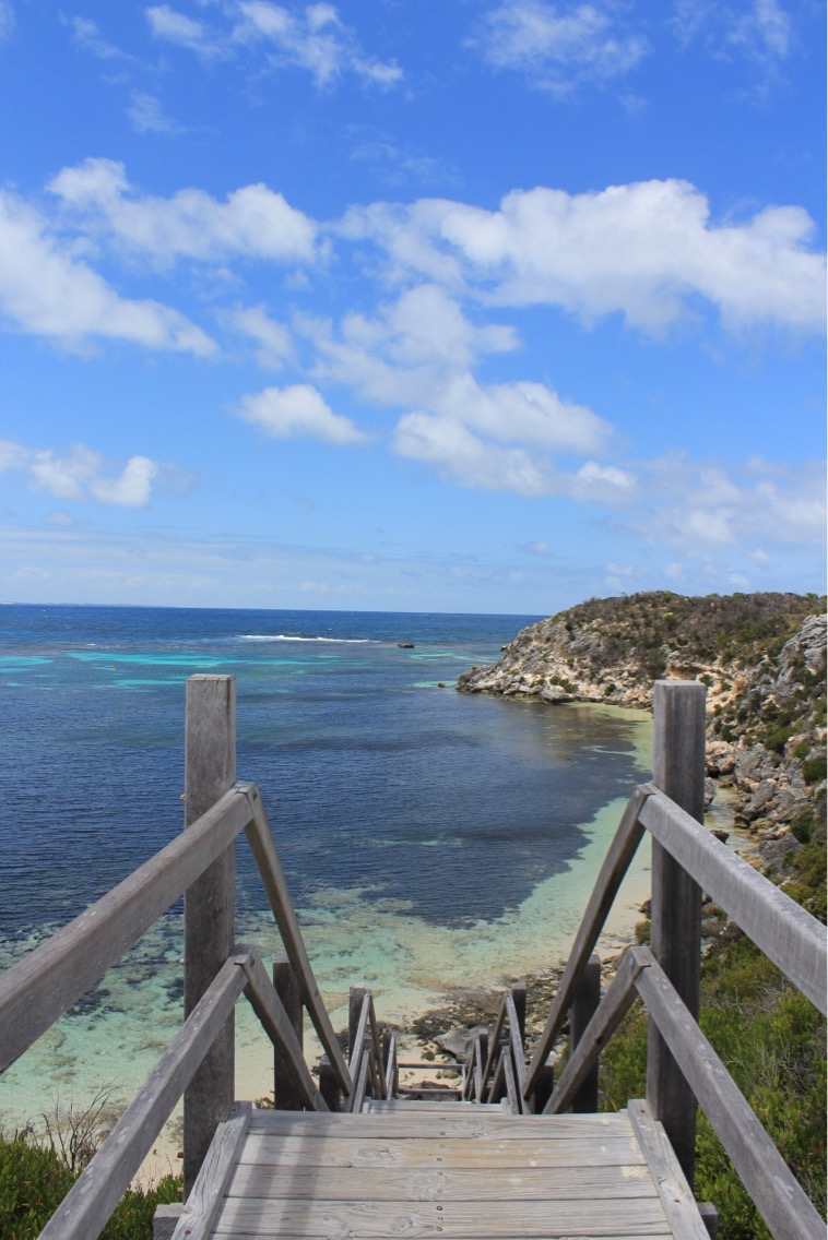 Steps down to the beach with blue skies and ocean views