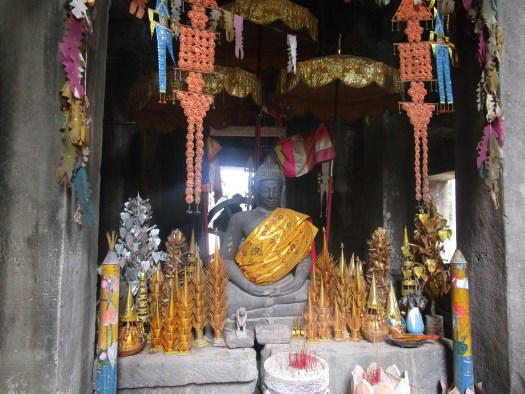 A small Buddhist shrine is heavily decorated with colourful objects and incense at Angkor Wat in Cambodia