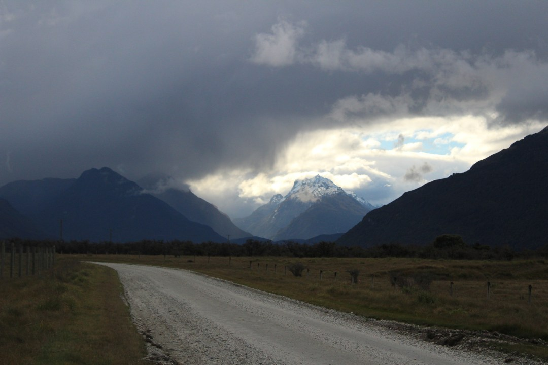 Storm clouds brew over an unmarked road with mountains in the distance