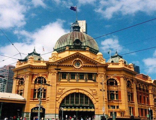 The yellow front of Flinders Street Station in Melbourne with busy pedestrians walking across the street