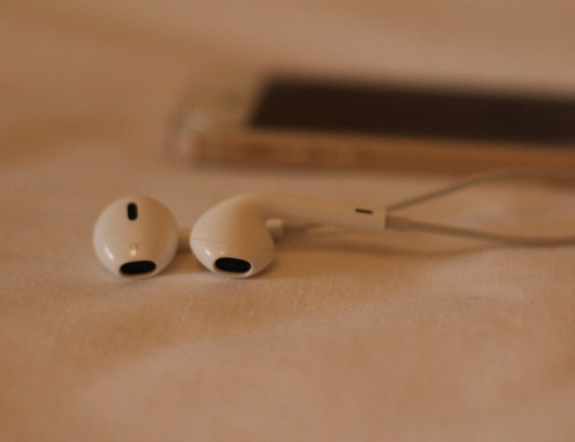 Close up of earbud headphones with iphone in background