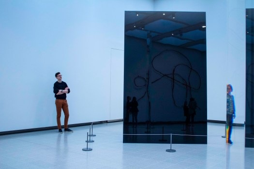 Man stands observing large contemporary art work