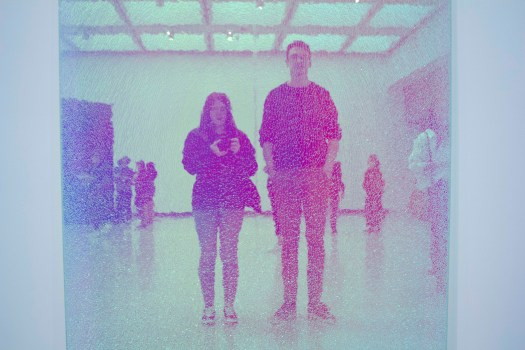Couple stand taking photo of their reflection in shattered, neon pink glass