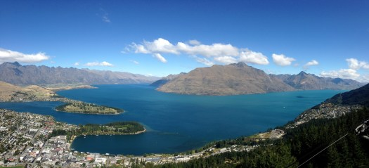 aerial view over queenstown town and mountains with the lake dominating the landscape